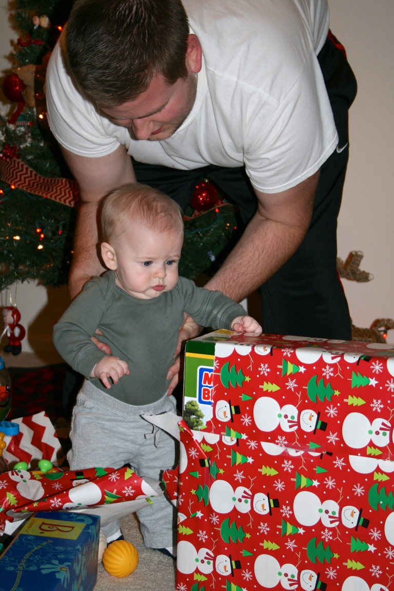 Daddy helping Grayson open his gifts from Santa.